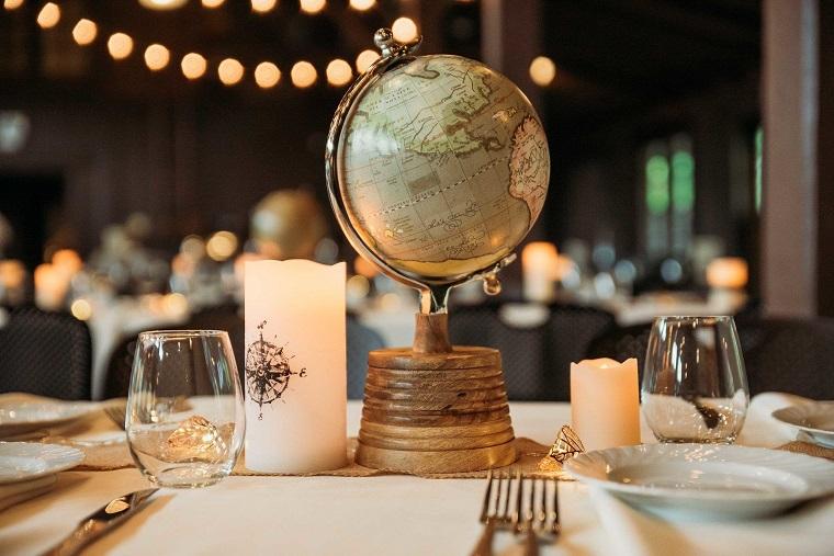 Tavola apparecchiata con piatti e posate, tavolo con centrotavola con un globo della terra