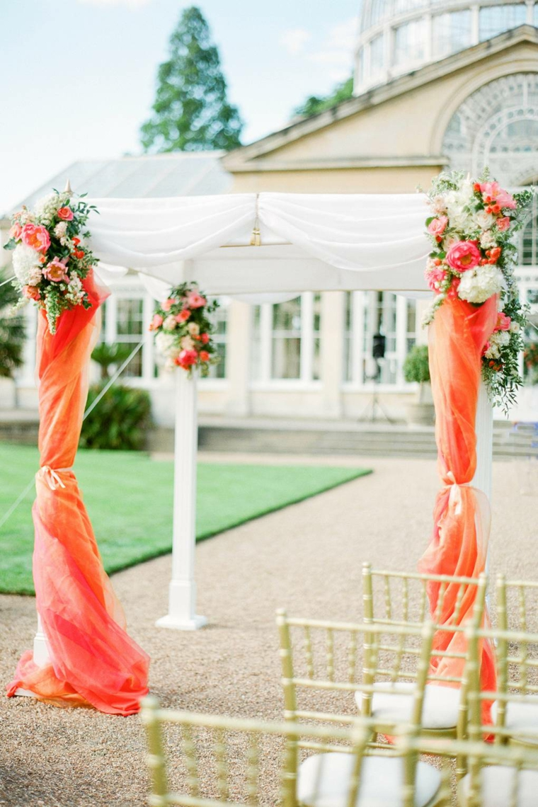Preparativi matrimonio, arca di legno con tulle arancione, sedie di legno per ospiti