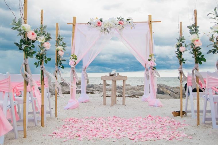 Arca di legno con tulle di colore rosa, petali di fiori sulla terra, preparativi matrimonio