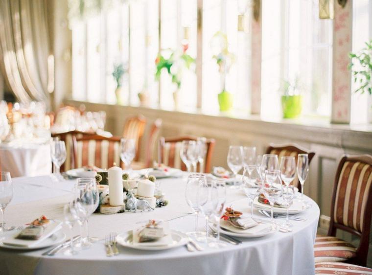 Idee matrimonio alternativo, tavola rotonda apparecchiata con bicchieri e piatti
