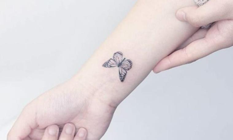 Tatuaggio farfalla, disegno di una farfalla, tattoo sul polso della mano di una donna