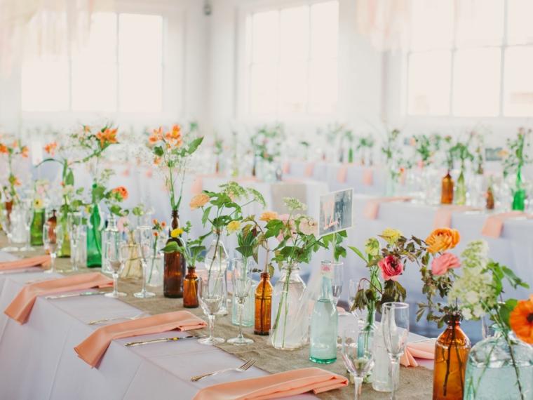 Idee matrimonio alternativo, centrotavola con bottiglie di vetro e fiori, tavola apparecchiata