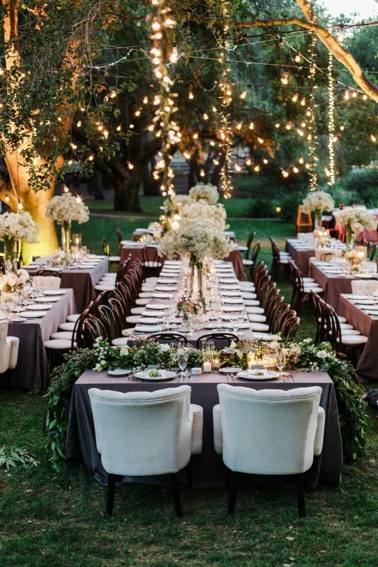 Organizzare un matrimonio, giardino con tavoli apparecchiati, albero con rami addobbati con luci