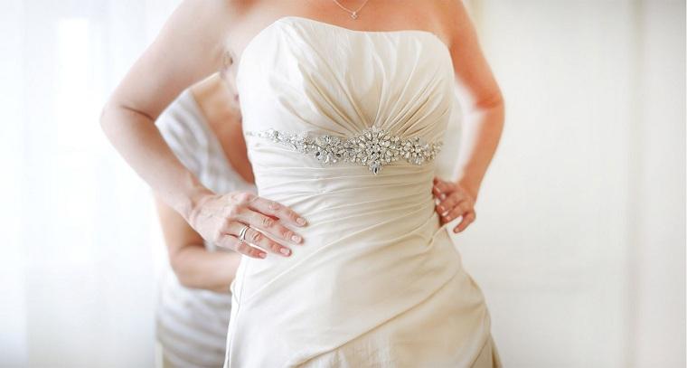 Donna che prova l'abito da sposa, vestito da sposa con decorazioni
