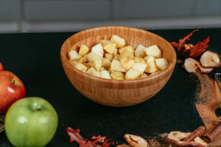 Apple pie ricetta, ciotola di legno con cubetti di mele, tavolo con ingredienti per crostata
