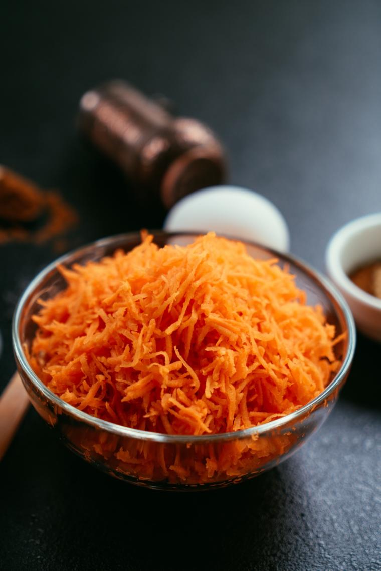 Ciotola con carote grattugiate, torta alle carote, ingredienti per torta camilla