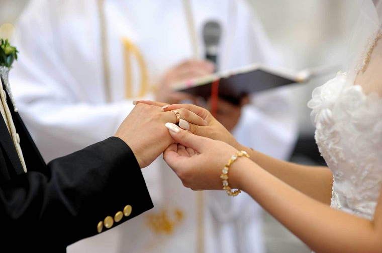 Donna che mette l'anello nuziale all'uomo, matrimonio con rito religioso