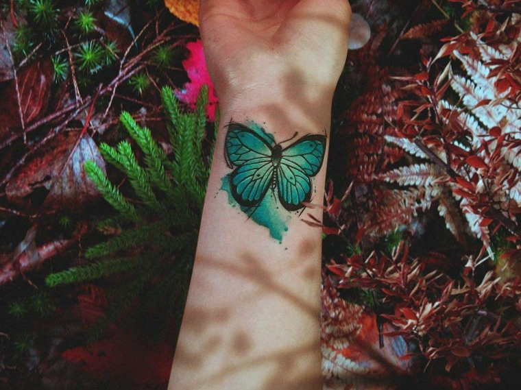 Farfalla tattoo, disegno colorato sul polso della mano, foglie di piante colorate
