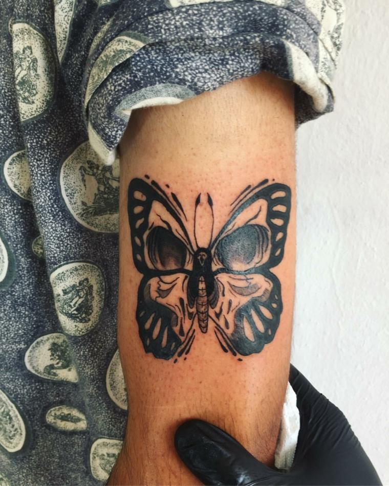 Uomo con tatuaggio di una farfalla di colore nero, uomo con tattoo sul braccio