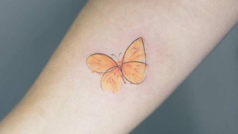 Disegno colorato di una farfalla, tatuaggio sul braccio di una donna