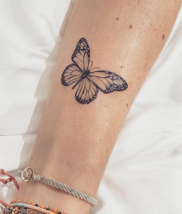 Immagini di farfalle in volo, avambraccio donna con tatuaggio di una farfalla