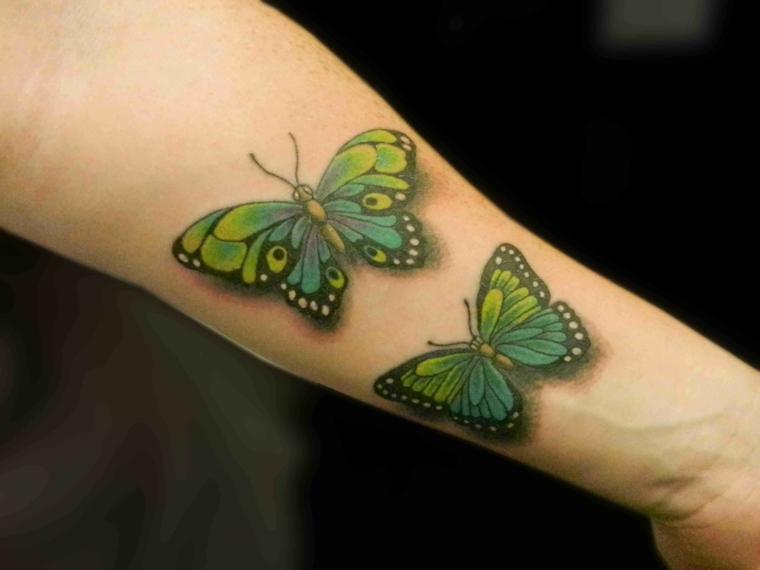 Disegni farfalle colorate, disegno di due farfalle di colore verde, tattoo sull'avambraccio donna