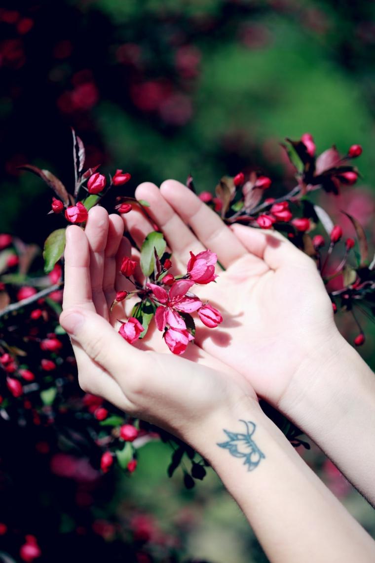 Farfalla significato, disegno tatuaggio sul polso della mano di una donna, petali di fiori