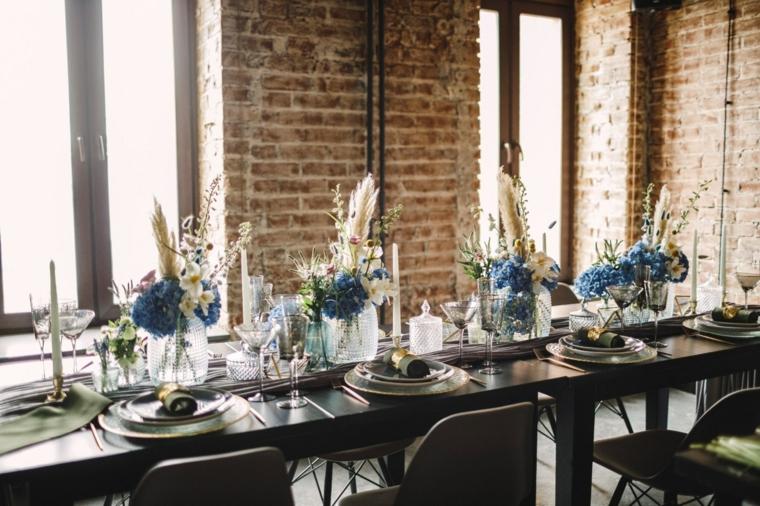 Tavola apparecchiata con piatti e segnaposto, centrotavola con vasi di fiori e candele