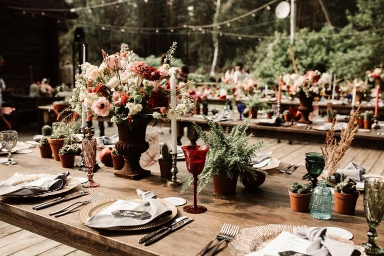 Centrotavola con fiori, tavola di legno apparecchiata con piatti e posate