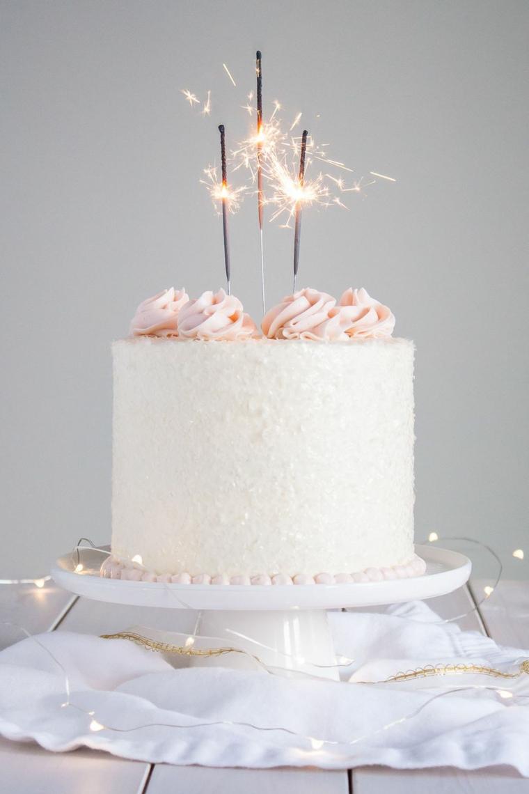 Torta rotonda con panna montata e topping candele, torta decorata con lucine