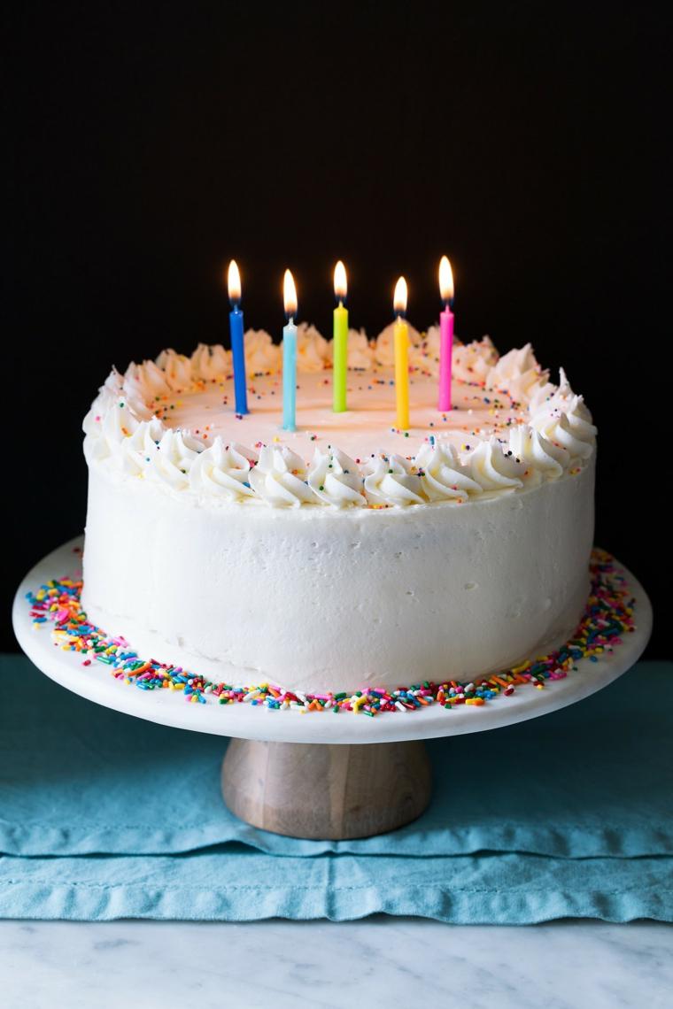 Torta rotonda decorata con candeline, torta con panna montata e codette di zucchero
