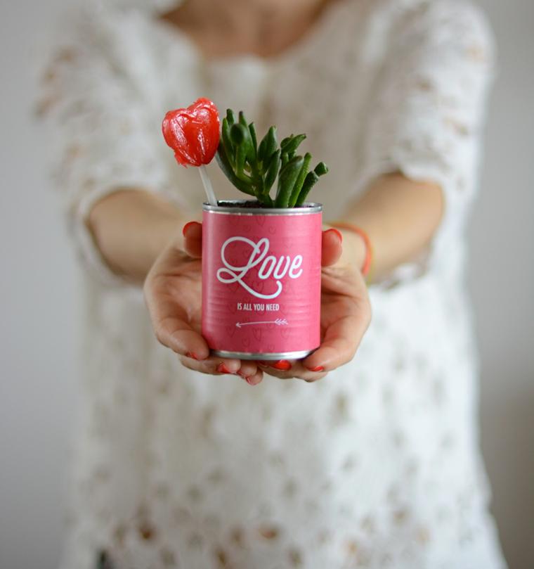 Donna con regalo per San Valentino, barattolo di latta con lecca lecca e piantina verde