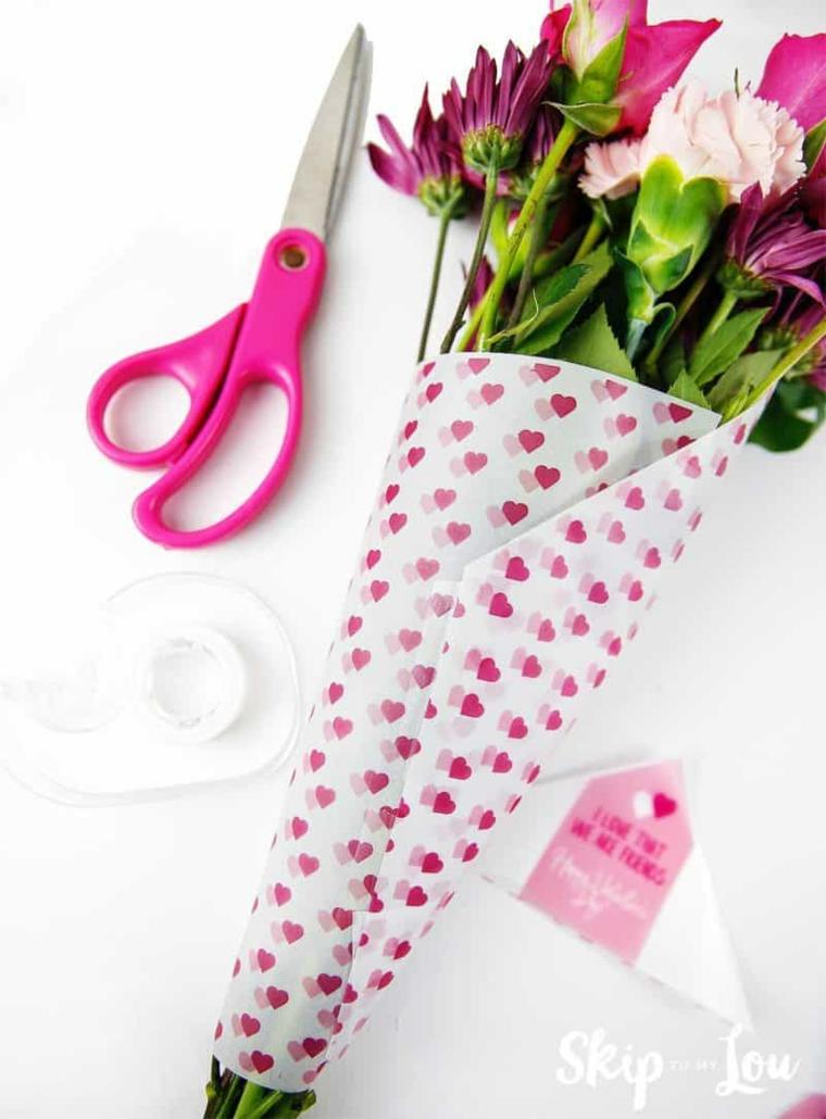 Regali da fare a San Valentino, bouquet di fiori con carta con motivi a cuore