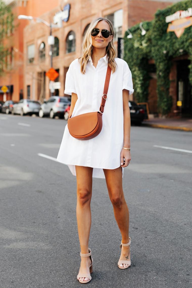 Ragazza con capelli medi di colore biondo, ragazza con abito bianco e borsa tracolla