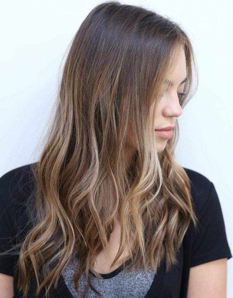 Capelli castani con riflessi, capelli lunghi con onde morbide dal colore biondo