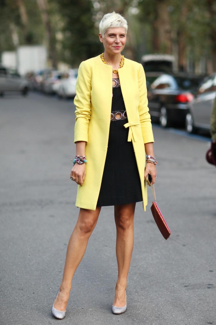 Taglio capelli corti 2020 donne 50 anni, donna che indossa un cappotto giallo