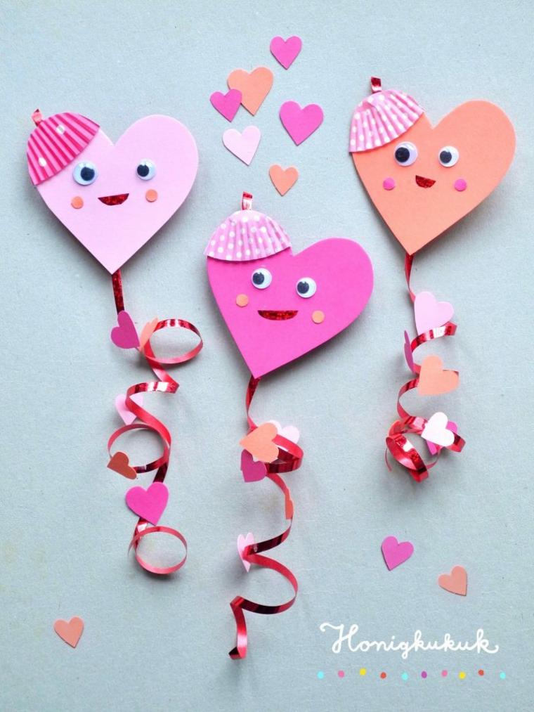 Regali per 14 febbraio, cuori di carta con faccine e nastro arricciato sotto con confetti