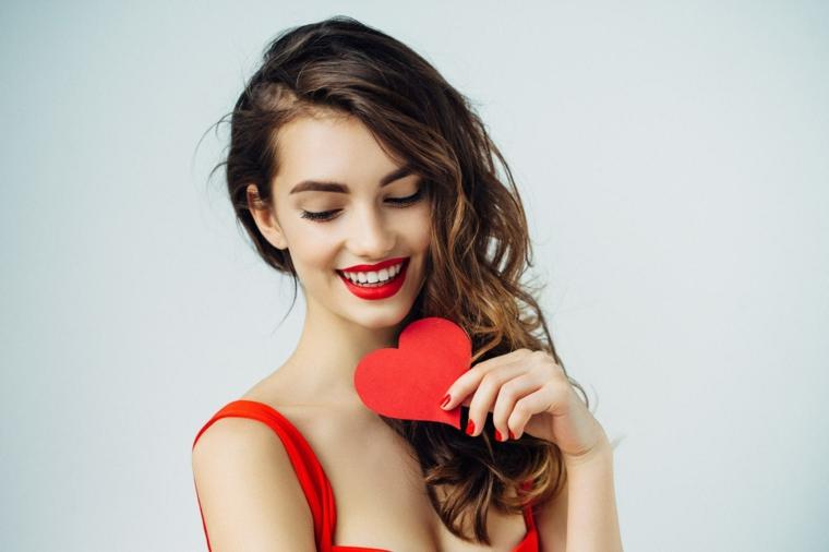 Donna che tiene un cuore rosso, ragazza con capelli lunghi e ricci, capelli castano caramello