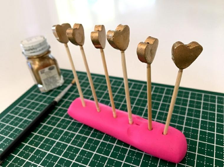 Idee regalo per san valentino, bastoncini di legno con cuori dipinti di colore oro