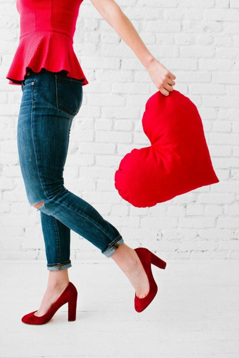 Cuscino imbottito a forma di cuore rosso, donna che tiene un cuscino