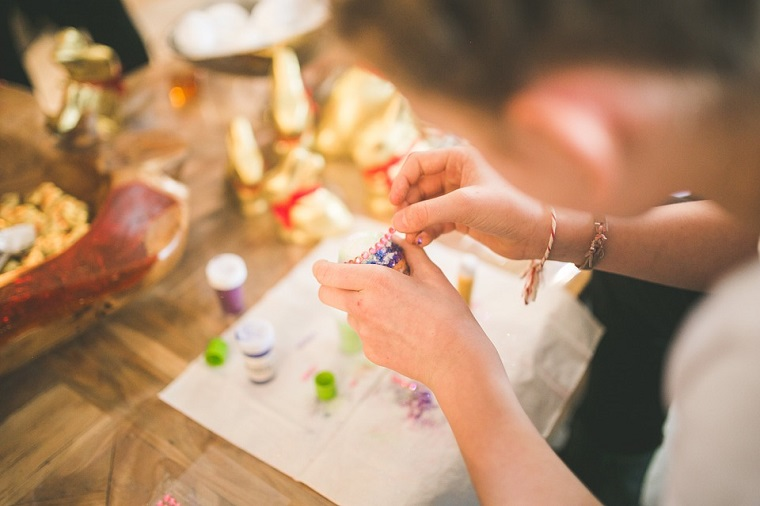 Bambina che incolla brillantini, decorazioni uova pasquali, lavoretti creativi per bambini