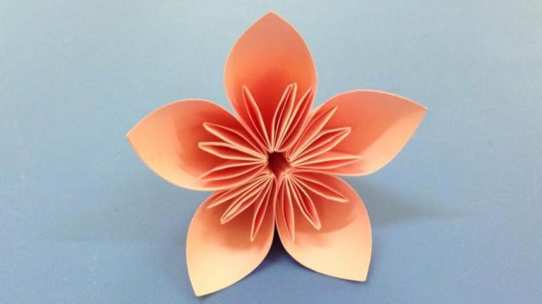 Origami istruzioni, piegare la carta origami di colore rosa per un fiore con petali