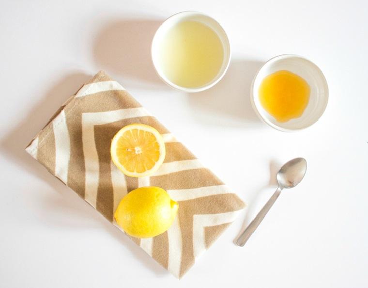 Limone tagliato a metà su un tovagliolo, succo di limone in ciotola, maschera per brufoli