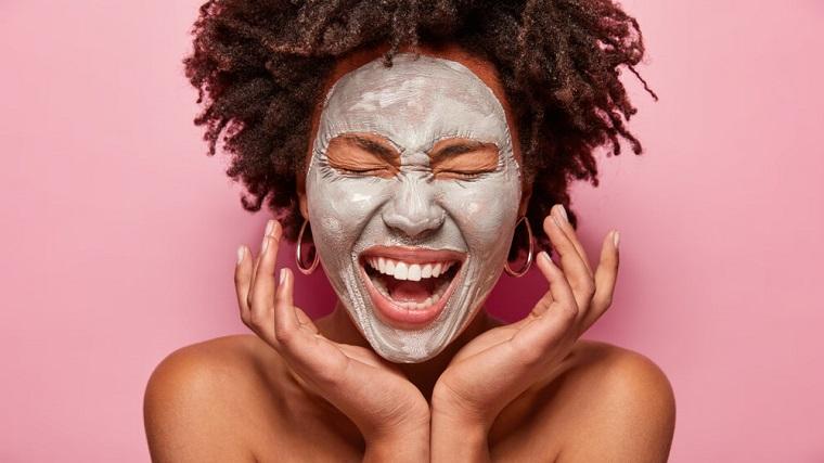 Maschera viso fai da te, donna con capelli ricci corti, maschera sul viso di una donna