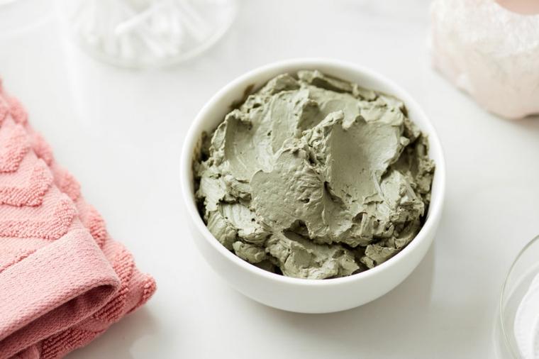 Ciotola con impasto di argilla verde, maschera purificante viso, tovagliolo rosa su un tavolo