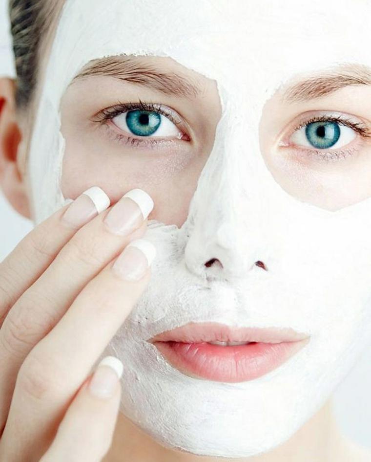 Maschera purificante viso, donna che si mette una crema di colore bianco
