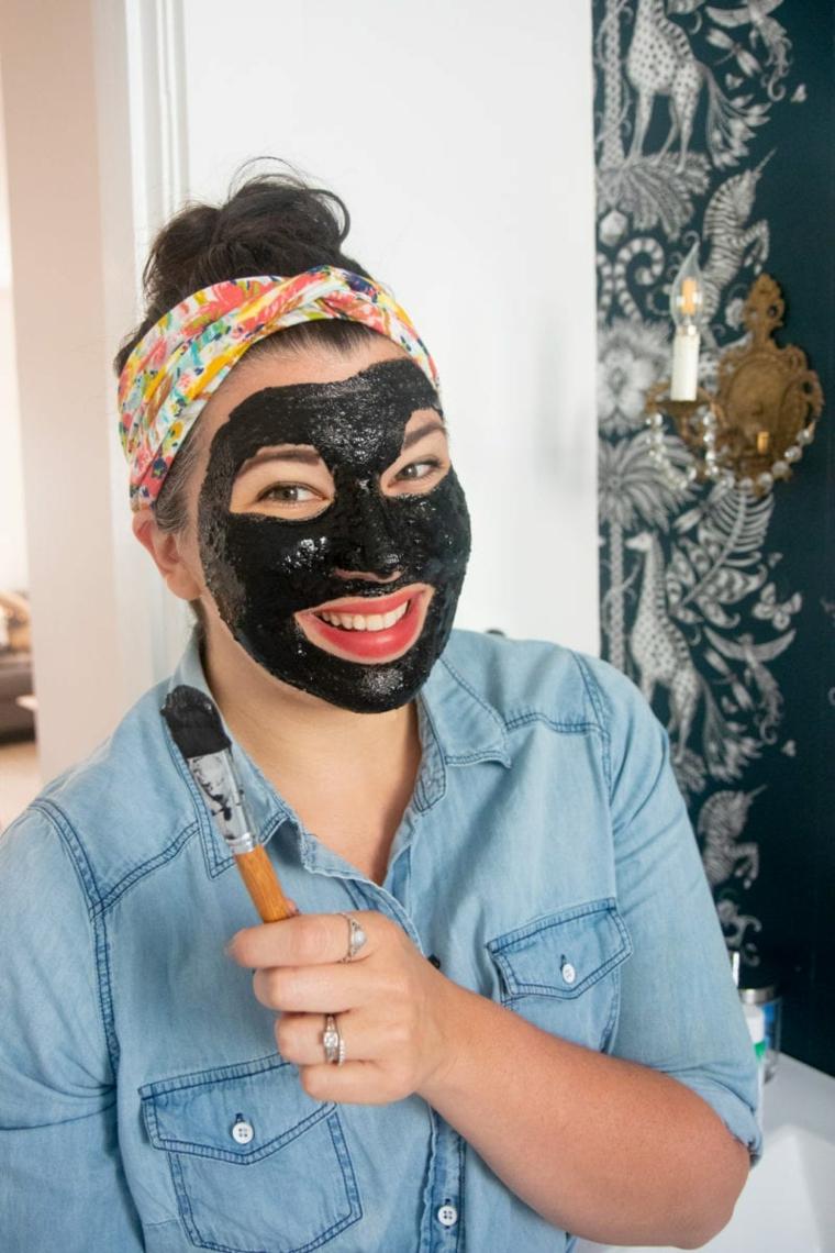 Maschera per brufoli, donna con maschera di colore nero che tiene un pennello