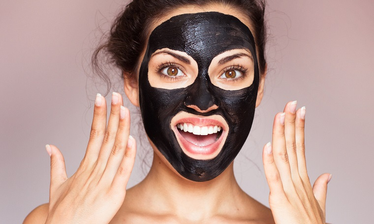 Donna con una maschera di colore nero sul viso, maschera viso idratante fai da te