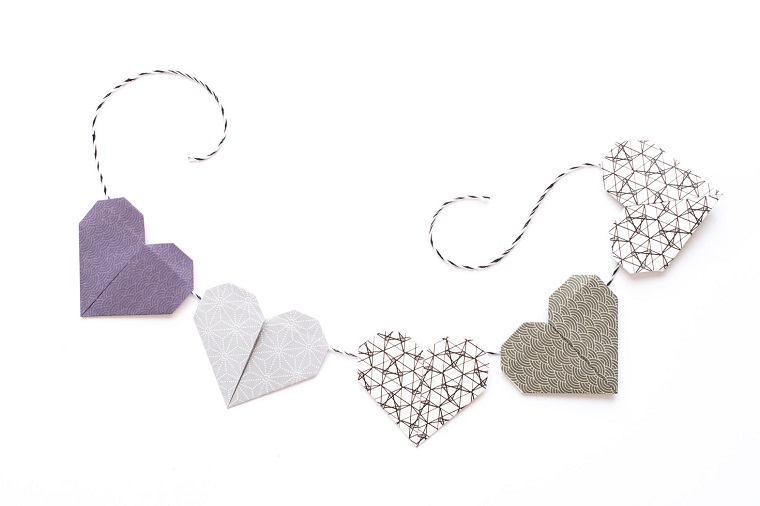 Origami semplici, ghirlanda di cuori di carta legati insieme con un filo