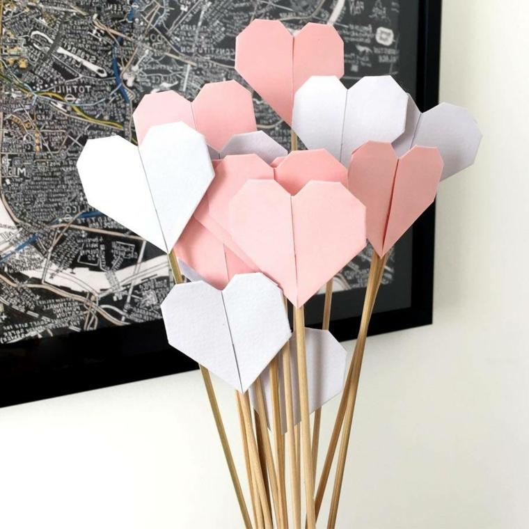 Bastoncini di legno con cuori di carta origami, origami cuore di foglio bianco e rosa