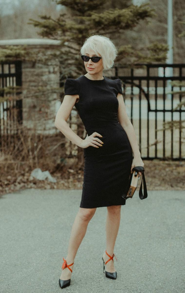 Capelli corti donna 2020, dona che indossa un tubino di colore nero, capelli taglio asimmetrico di colore biondo