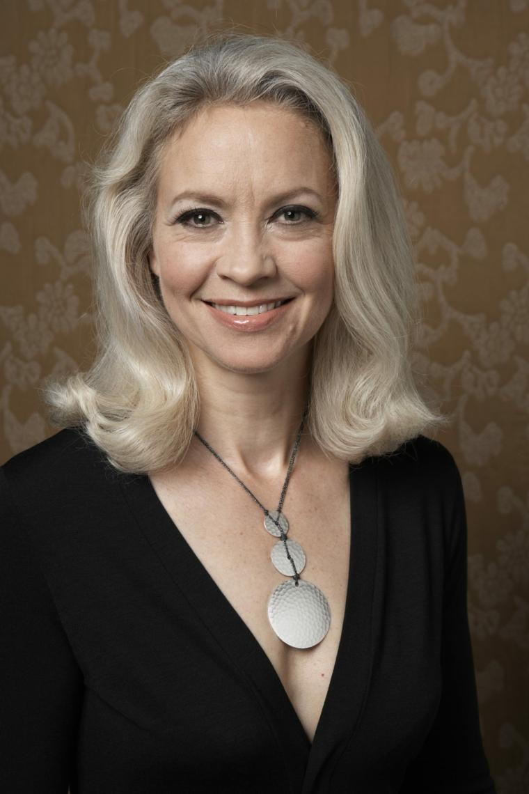 Donna con un taglio long bob di colore biondo platino, donna che indossa un abito nero