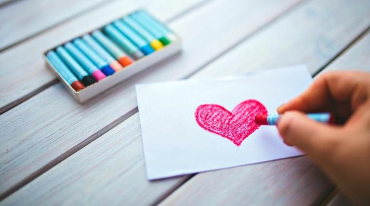 Cosa regalare a san valentino, bigliettino con disegno di un cuore, scatola con pastelli