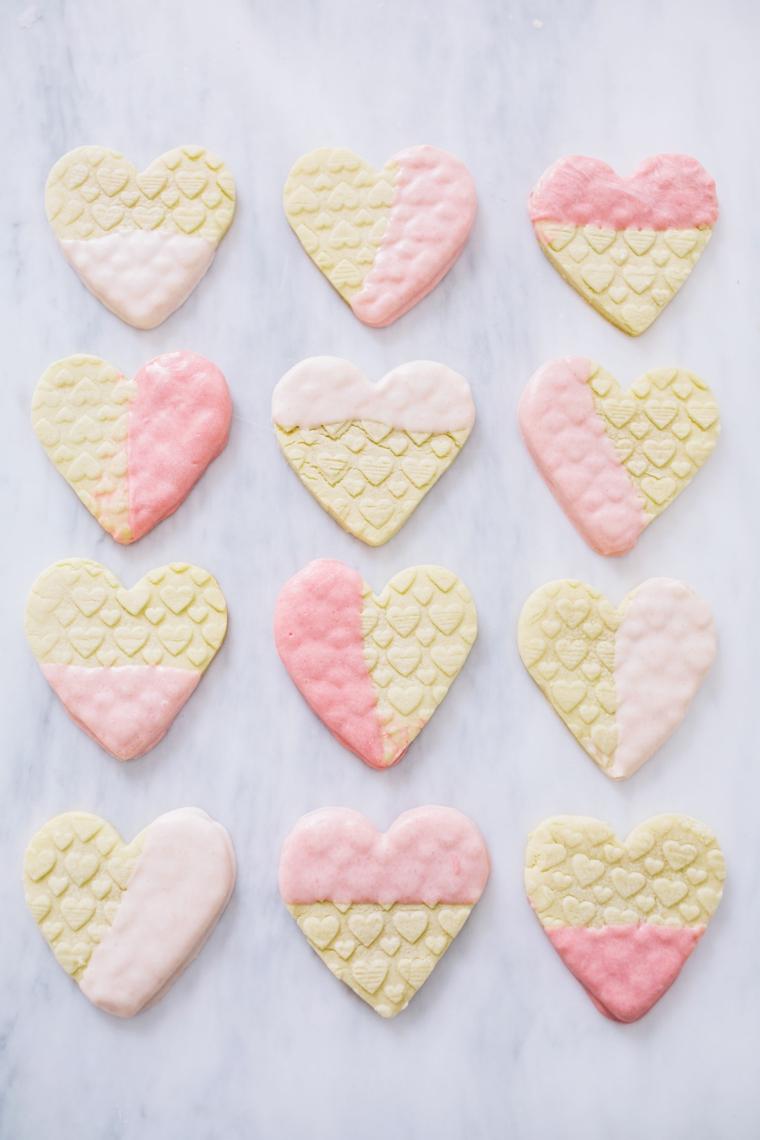 Regali da fare a San Valentino, biscotti a forma di cuore immersi in cioccolato rosa