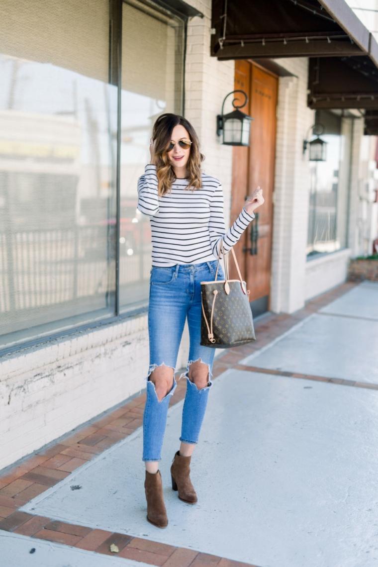 Ragazza con jeans chiari con strappi, acconciatura capelli medi di colore castano caramello