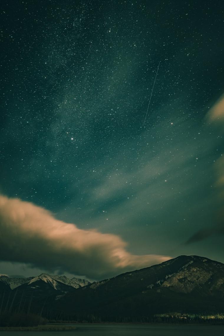 Foto di montagne innevate con cielo stellato, gli sfondi più belli del mondo