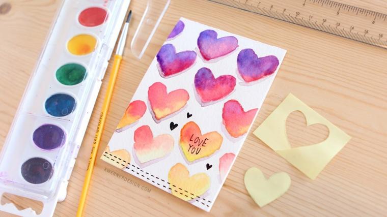Bigliettino con disegno di cuori, pallete di colori ad acquarello con pennello