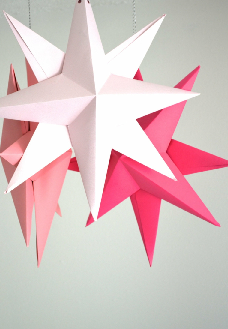Fogli di carta per origami piegati a forma di stelle, fili a cui sono appese delle stelle di carta