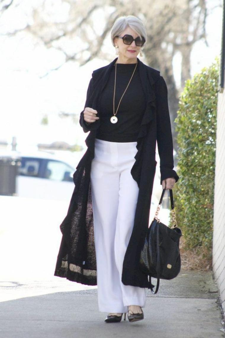 Tagli capelli corti donna, donna che cammina con capelli biondi e frangetta laterale