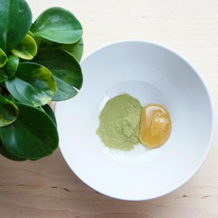 Maschera idratante viso fai da te, piatto con polvere verde e miele